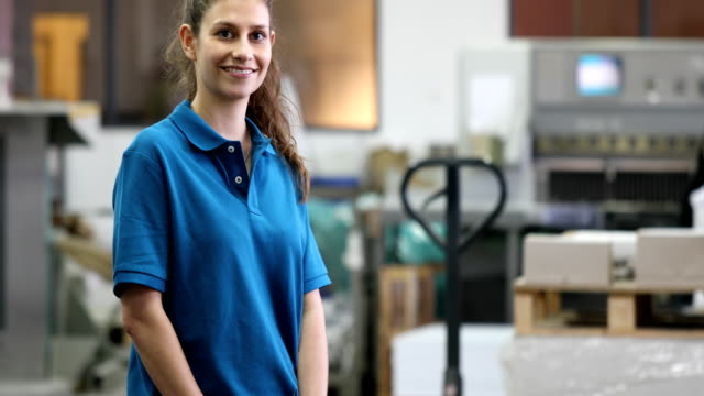 Confident female worker standing at printing plant