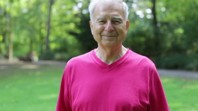 confident fit senior man smiling in park - pink shirt stock videos and b-roll footage