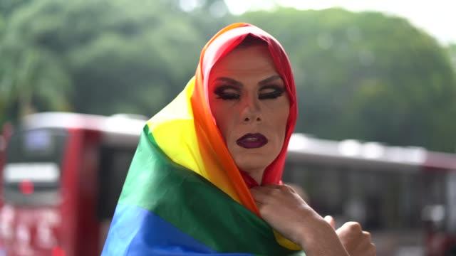 vídeos de stock, filmes e b-roll de confiante rapaz gay, segurando a bandeira de arco-íris - gabar se
