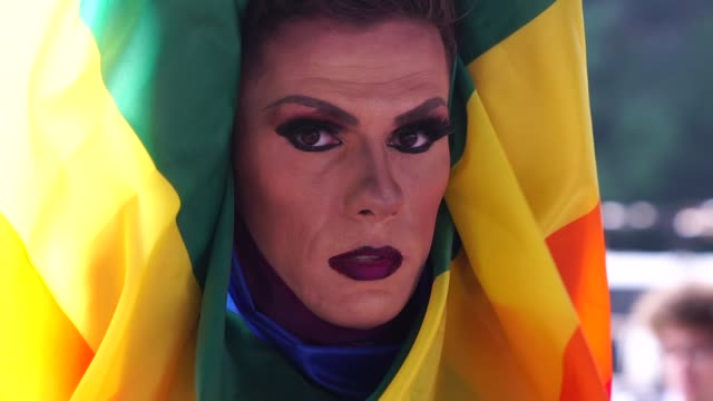 confident gay boy holding rainbow flag - drag queen stock videos and b-roll footage
