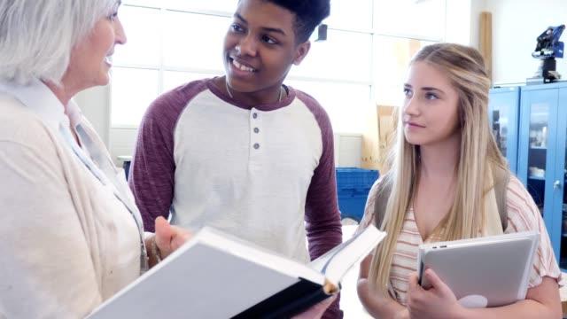 vidéos et rushes de le professeur de lycée confiant explique le concept de science aux étudiants - petite amie