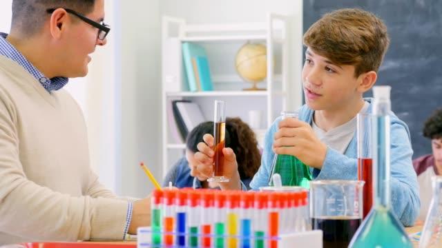 Confident Hispanic high school student and teacher in chemistry class