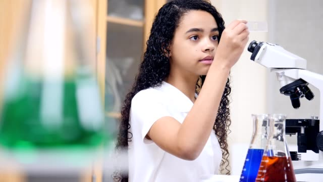 confident junior high school girl uses microscope during chemistry lab - junior high student stock videos and b-roll footage