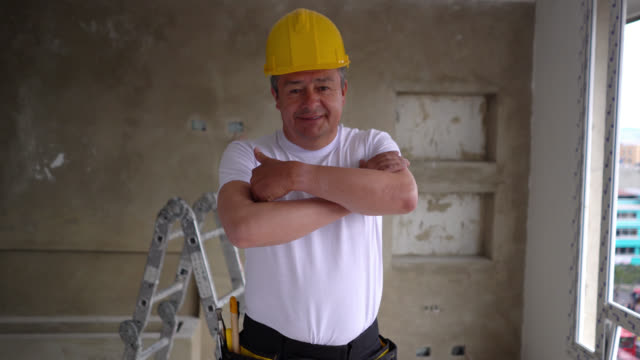 confident latin american adult construction worker at an apartment smiling at camera crossing arms - craftsperson stock videos & royalty-free footage