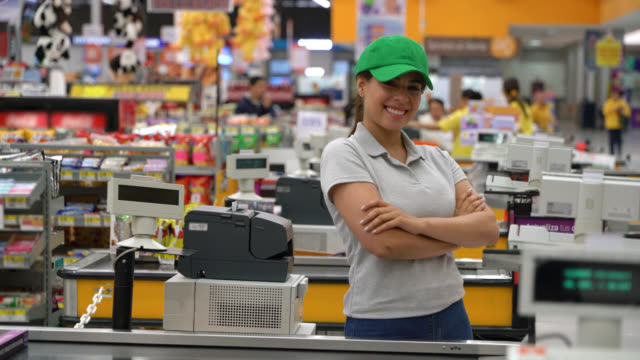 confident latin american cashier standing at the check out while facing camera with arms crossed - retail manager stock videos & royalty-free footage