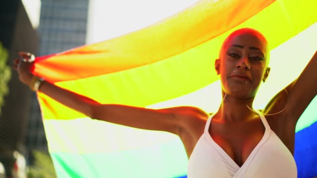 confident lesbian walking with arms open holding rainbow flag during lgbtqi parade - pride stock videos & royalty-free footage