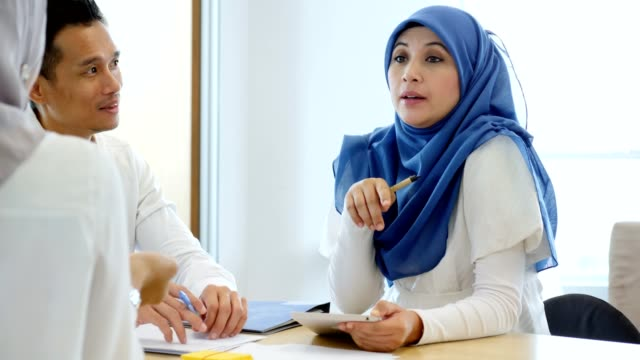 Confident Malaysian businesswomen facilitates staff meeting