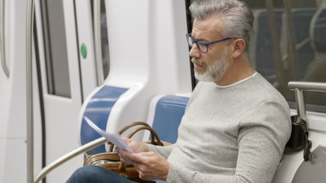 confident male commuter reading document in train - mature adult stock videos & royalty-free footage