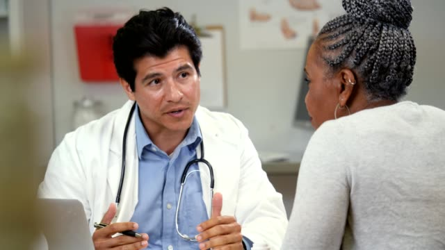 confident male doctor discusses test results with senior female patient - males stock videos & royalty-free footage