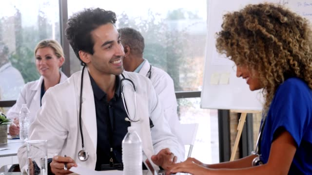 confident male doctor meets with female colleague - scrubs stock videos & royalty-free footage