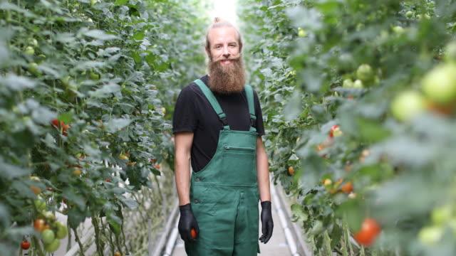 Zuversichtlich männlichen Bauern im Gewächshaus stehen