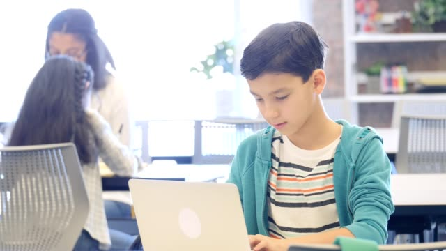 confident male middle school student uses laptop during class - middle class stock videos and b-roll footage