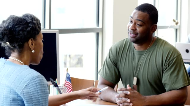 confident male military soldier talks with loan officer at a local bank - bank manager stock videos & royalty-free footage