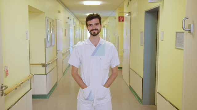confident male nurse standing in medical clinic - hands in pockets stock videos & royalty-free footage