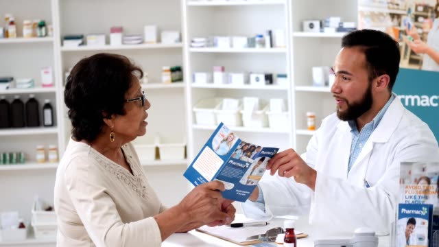 confident male pharmacist reviews pharmacy services with customer - flyer leaflet stock videos and b-roll footage