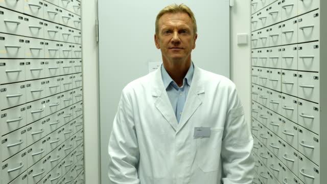 zuversichtlich männlichen apotheker lächelnd im lagerraum - arme verschränkt stock-videos und b-roll-filmmaterial