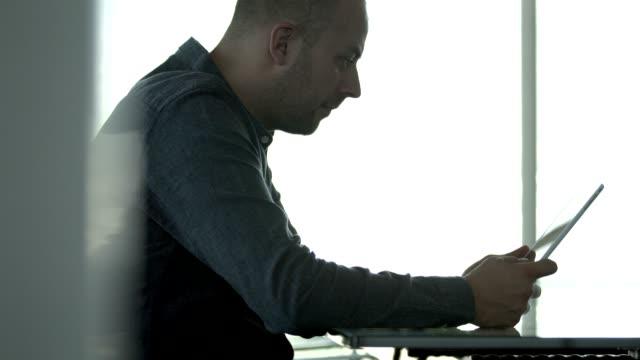 vídeos de stock, filmes e b-roll de confident male professional using digital tablet - desaparecer gradualmente