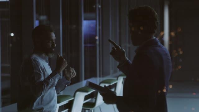 vídeos de stock e filmes b-roll de confident male professionals discussing strategy - dark