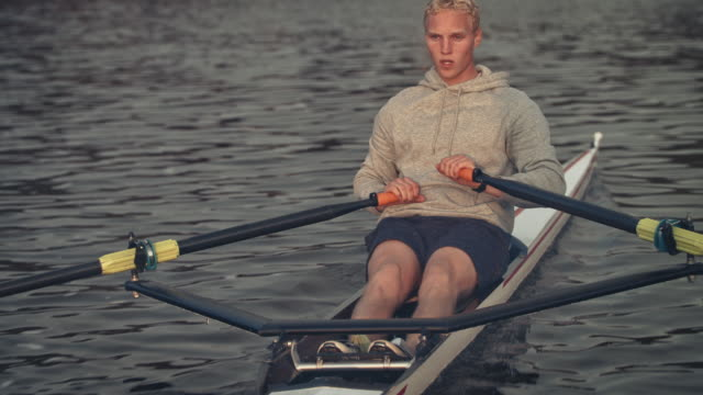 confident male rowing boat in river - sculling video stock e b–roll
