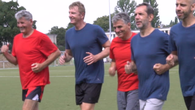 confident male soccer players jogging on playing field - mature men stock videos & royalty-free footage