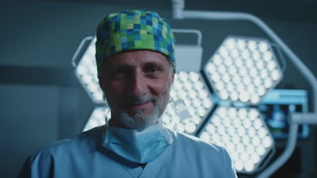 vídeos y material grabado en eventos de stock de cirujano masculino confiado que opera en la sala de emergencias - guantes de protección