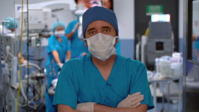 zuversichtlicher männlicher chirurg trägt eine schutzmaske, während er vor der kamera steht und die arme in einem operationssaal kreuzt - op mundschutz stock-videos und b-roll-filmmaterial