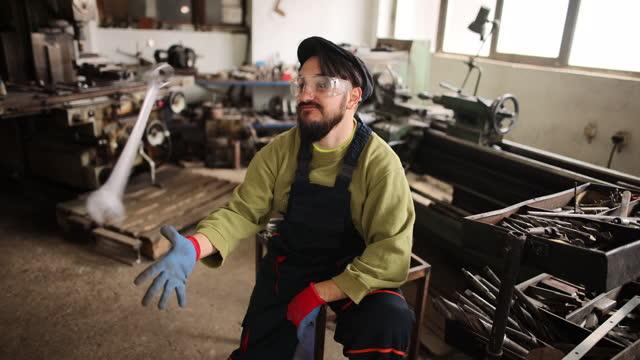 zuversichtlicher männlicher arbeiter spielt mit schraubenschlüssel in der fabrik - werkzeug stock-videos und b-roll-filmmaterial