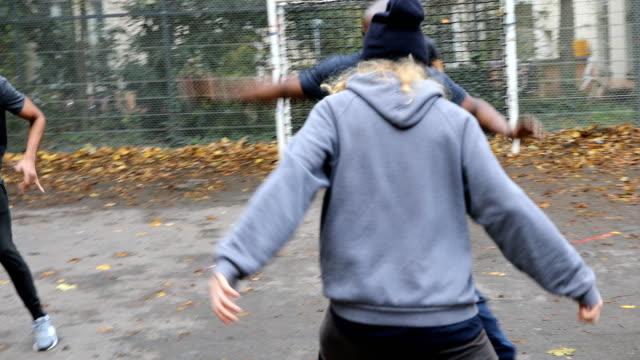 vidéos et rushes de homme confiant dribbler le ballon en direction de but de football - plaque rue