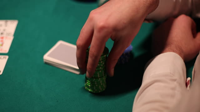 confident man shuffling poker chips in hand during poker game - gambling chip stock videos & royalty-free footage