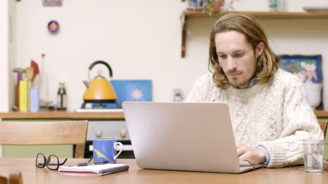 zuversichtlich mann mit laptop am tisch in der küche - junger mann allein stock-videos und b-roll-filmmaterial