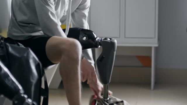 Confident man with prosthetic leg getting changed