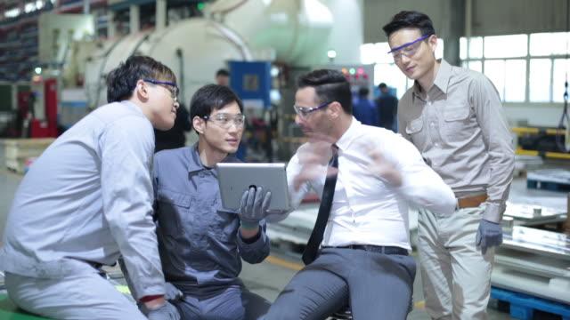confident manager and engineers talking in factory,hd - skjorta och slips bildbanksvideor och videomaterial från bakom kulisserna