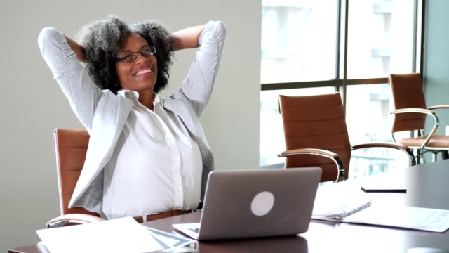 confident mature businesswoman puts the finishing touches on document - woman hands behind head stock videos & royalty-free footage