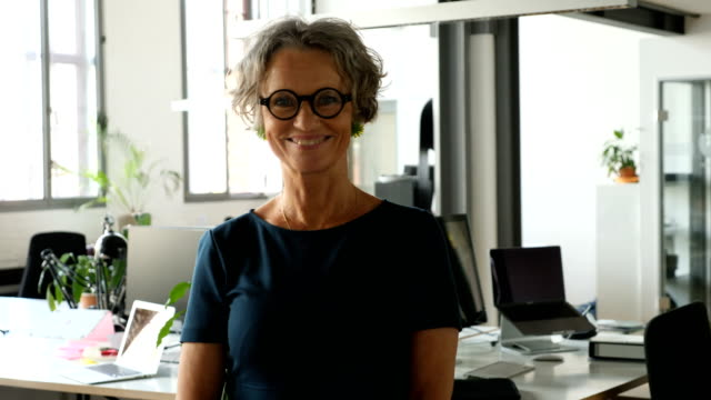 confident mature businesswoman standing at office - short hair stock videos & royalty-free footage