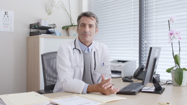 confident mature doctor with computer at desk - only mature men video stock e b–roll