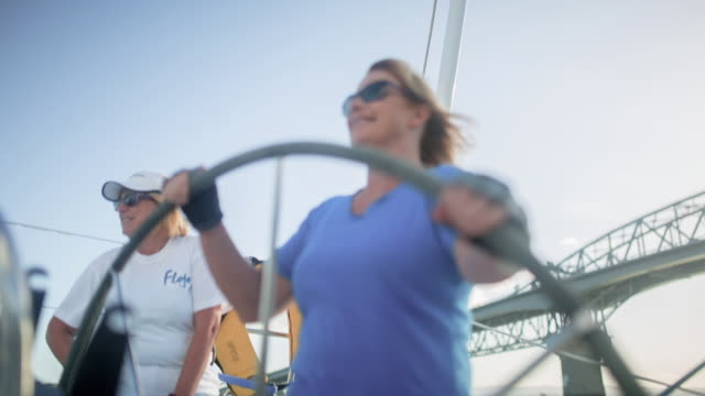Confident mature female sisters in control of the helm wheel of luxury sailing yacht