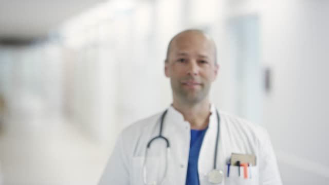 vídeos de stock e filmes b-roll de confident mature male doctor standing at hospital - fade in