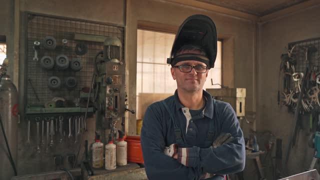 confident mid adult engeener at his metal workshop - welding helmet stock videos & royalty-free footage