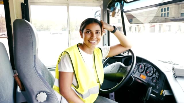 confident mid adult hispanic female school bus driver - driver occupation stock videos & royalty-free footage