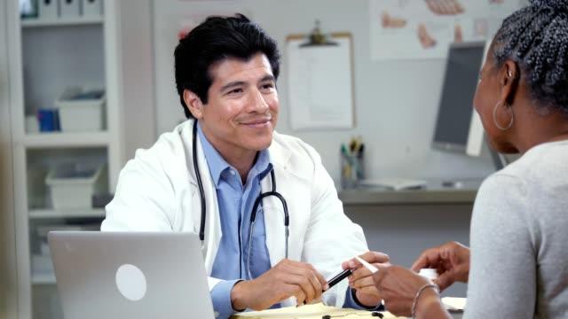 confident mid adult hispanic male doctor talks with senior patient - prescription medicine stock videos & royalty-free footage