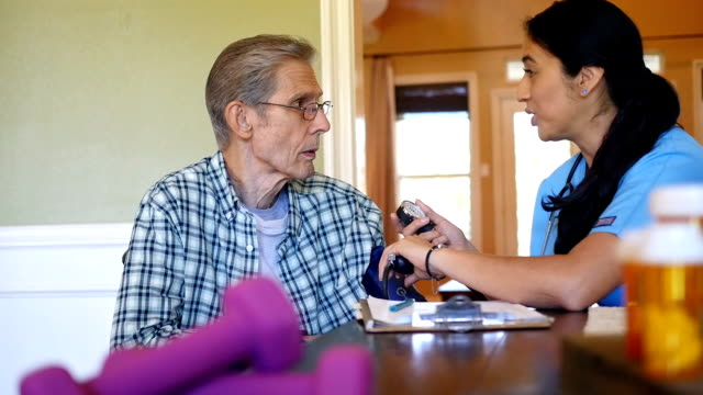 confident mid adult hispanic nurse checks senior patient's blood pressuring during home visit - prescription medicine home stock videos & royalty-free footage