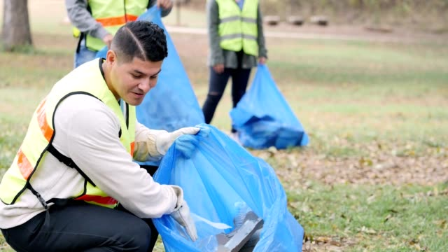 Confident mid adult man cleans up park with his neighbors