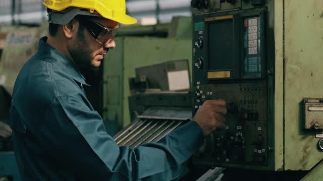 vídeos de stock, filmes e b-roll de homem confiante do oriente médio na fábrica operando máquina complexa em linha de fábrica. conceito de fabricação. - estrutura construída