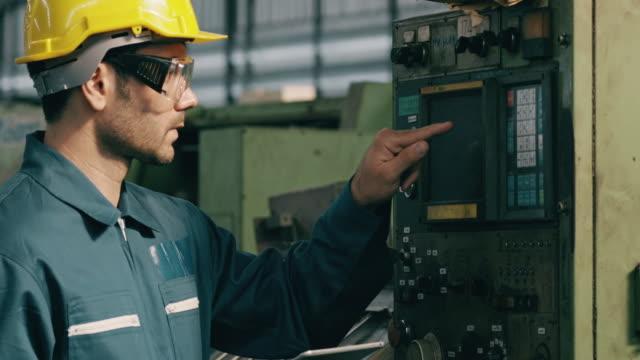 vidéos et rushes de homme confiant du moyen-orient dans l'usine utilisant la tablette pour l'aider à actionner la machine complexe dans la ligne d'usine. concept de fabrication. - manufacturing occupation