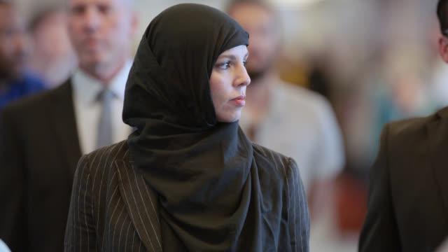 vídeos y material grabado en eventos de stock de confident middle eastern businesswoman looks around while walking through crowded airport terminal. - inmigrante