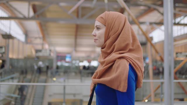Confident Middle Eastern female traveler walks through airport terminal near entrance.