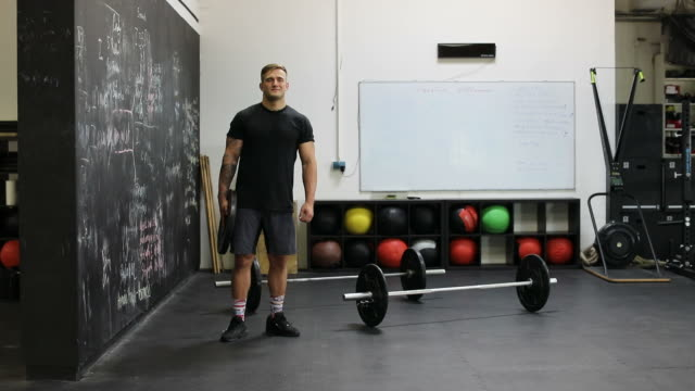 Confident muscular man holding weight in gym