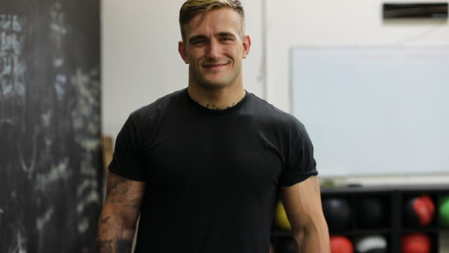 Confident muscular man smiling in gym