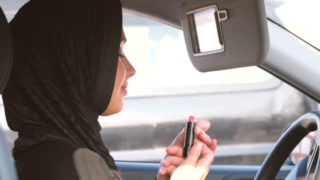 zuversichtliche muslimische dame trägt lippenstift im auto - lippenstift stock-videos und b-roll-filmmaterial