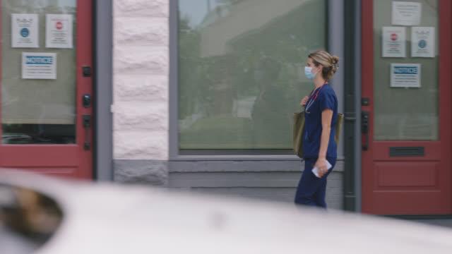 ws confident nurse walks down sidewalk looking at phone, opens door to enter building - entering stock videos & royalty-free footage